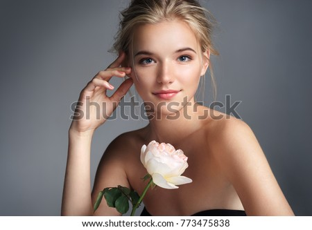 Beautiful young girl. Photo of blonde girl with rose on grey background. Skin care concept