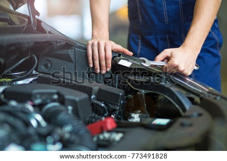 Mechanic working on engine in auto repair shop  #773491828