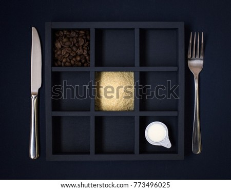 knife and fork near a black square plate with coffee beans #773496025