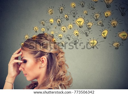 Young woman thinking with concentrated having many ideas with backdrop of burning lightbulbs.  Royalty-Free Stock Photo #773506342