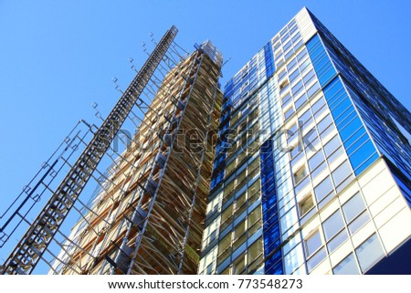 tall building reaching up to the blue sky stock photo #773548273
