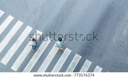 the From the top crosswise view of people walk on street pedestrian crossroad in the city street ,bird eye view. #773576374