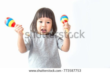 Little cute asian girl playing the maracas, preschool play group, music learning by doing and education concept #773587753