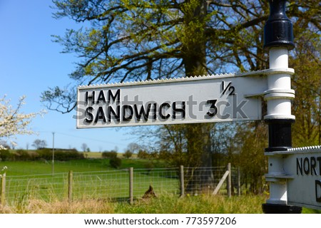 Landscape orientation of amusing funny fingerpost road sign post with village of Ham and town of Sandwich in Kent, England