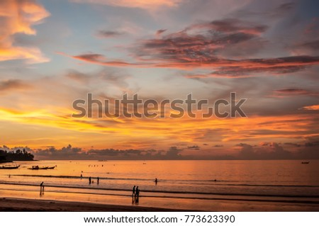 Beautiful sunset on the coast with light with a luminous cloud. Silhouettes of people walking on the beach. #773623390