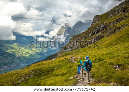 Two women hikers on the Eiger trail in the Alps mountains above Lauterbrunnen, Switzerland.  The village of Grindelwald is in the background. #773691742