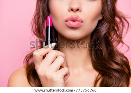 Air kiss for you. Close up cropped shot of femenine gorgeous charming adorable lady with amazing wavy hair do, tube of hard pink pomade in arm. Pampering, lips correction concept #773756968