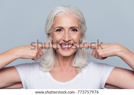 Concept of having strong healthy straight white teeth at old age. Close up portrait of happy with beaming smile female pensioner pointing on her perfect clear white teeth, isolated on gray background #773757976