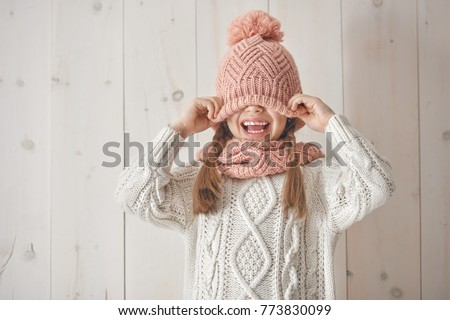 Winter portrait of happy little girl wearing knitted hat, scarf and sweater. Child on white wooden background. Fashion concept.