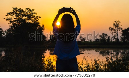 silhouette of a woman holding a smartphone taking pictures outside during sunrise or sunset. Travelling and vacation concept.