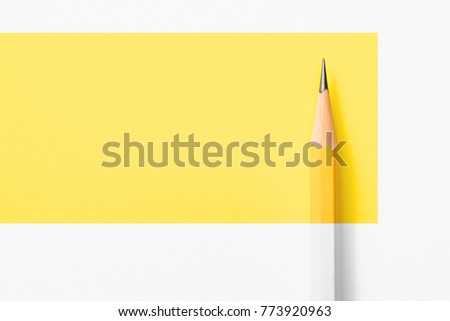 Minimalist template with copy space by top view close up macro photo of wooden yellow pencil put on yellow paper. Flashlight make difference between pencil and yellow paper by highlight and shadow. #773920963