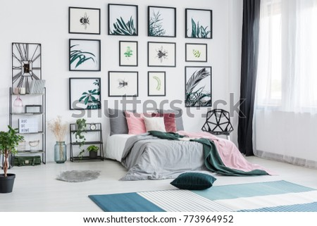 Blue carpet in spacious bright botanic bedroom with pink pillows on bed between shelf with plant and chair #773964952