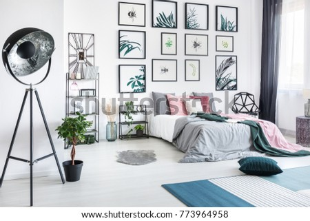 Designer metal lamp in spacious bedroom with plant and gallery of posters above king-size bed #773964958
