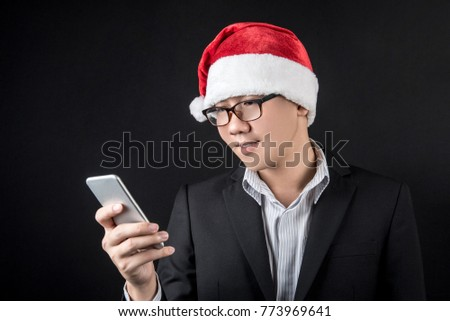Young Asian businessman wearing suit and santa hat using smartphone on black background, male entrepreneur in christmas holiday and new year party concepts #773969641