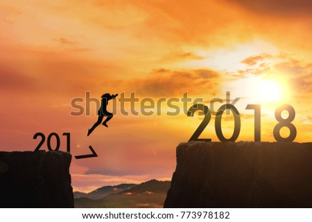 The woman jumping from 2017 cliff to 2018 cliff on sunrise time : meaning to going to year 2018 #773978182
