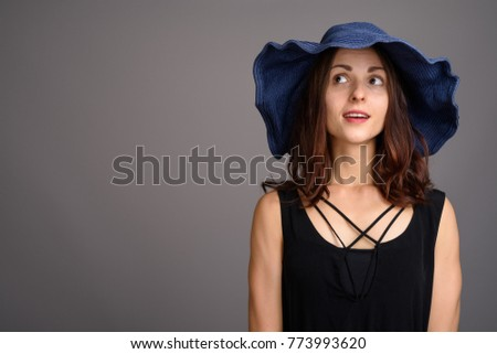 Studio shot of young beautiful woman against gray background #773993620