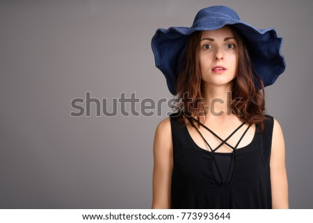 Studio shot of young beautiful woman against gray background #773993644