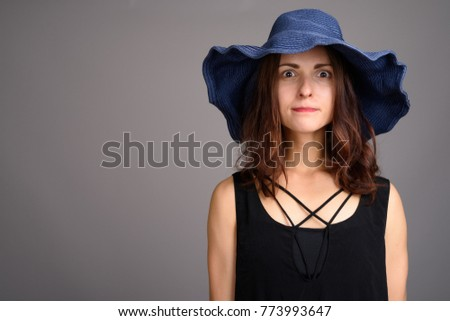 Studio shot of young beautiful woman against gray background #773993647