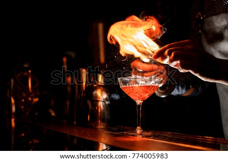 Barman`s hands making a fresh alcoholic cocktail with a smoky note on the dark bar counter #774005983