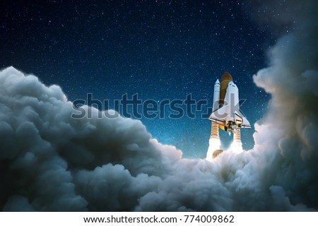 Rocket takes off in the starry sky. Spaceship begins the mission. Space shuttle taking off on a mission.  Royalty-Free Stock Photo #774009862