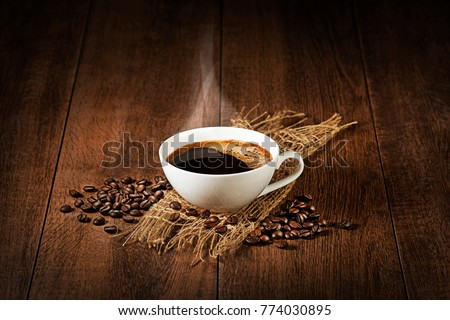 Coffee cup with smoke and beans on wooden table. Copyspace for your text #774030895