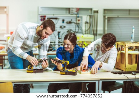 Young students of robotics preparing robot for testing in workshop #774057652
