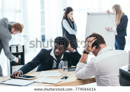 group of tired businesspeople in conference hall at office #774066616