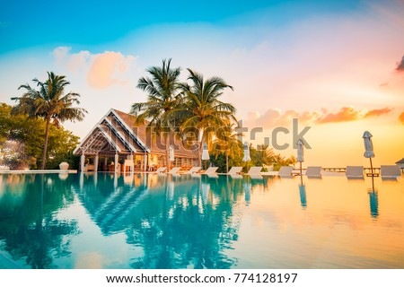 Beautiful poolside and sunset sky. Luxurious tropical beach landscape, deck chairs and loungers and water reflection. Royalty-Free Stock Photo #774128197