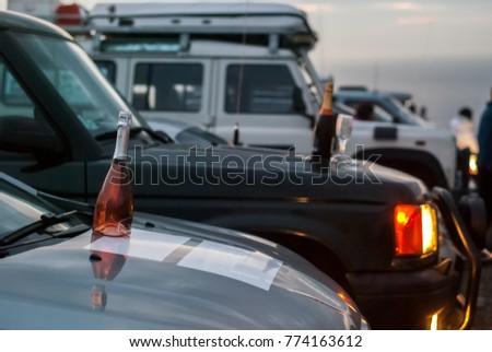 Bottles of wine on the hoods of cars at dusk #774163612