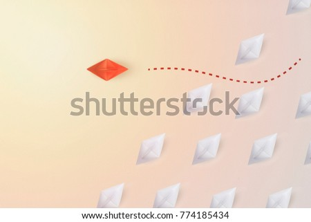 Business concept  as a group of paper ship in one direction and with one individual pointing in the different way as icon for innovative solution. #774185434