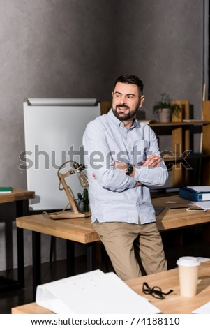 smiling businessman with crossed hands leaning on table in office and looking away #774188110