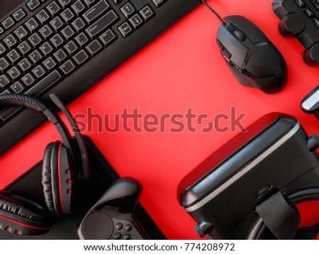 gamer workspace concept, top view a gaming gear, mouse, mouse mat, keyboard, joystick, headset, on red table background with copy space