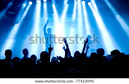 silhouettes of concert crowd in front of bright stage lights #77422090