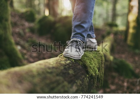 Woman walking on a log in the forest and balancing: physical exercise, healthy lifestyle and harmony concept