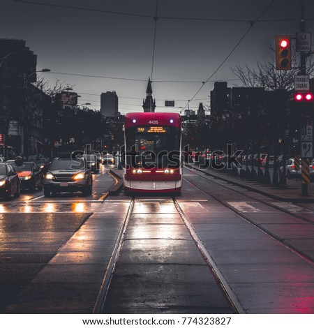 TORONTO STREETCAR - Toronto transit streetcar stopped at red light in downtown traffic at nightfall. Face-on view of train/tram from tracks. Rainy streets with muted colors. Toronto, Ontario, Canada Royalty-Free Stock Photo #774323827