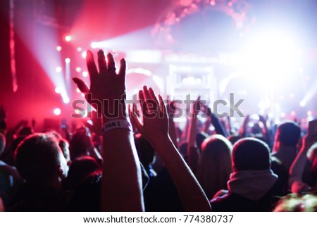 shiny rainbow confetti during the concert and the crowd of people silhouettes with their hands up. Dark background, smoke, concert spotlights. Bright lights #774380737