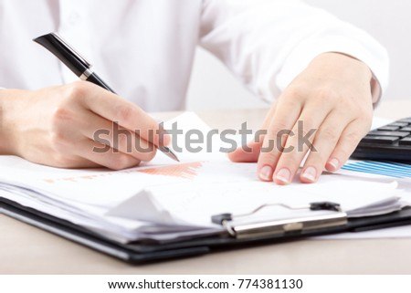 Close up of female accountant or banker making calculations. Savings, finances and economy concept #774381130