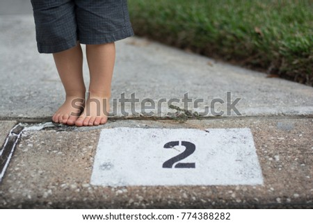 a little boy standing by a number 2 address  #774388282