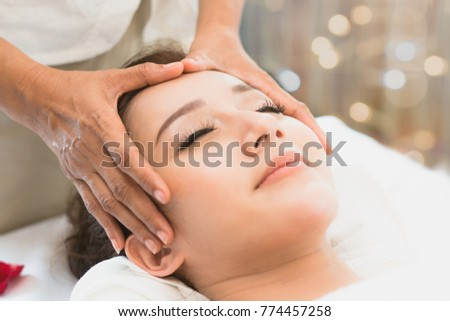 Facial massage in spa salon. Relaxation Beautiful woman lying on the bed and doing facial treatment in spa salon by masseur. Selective focus on thumb of masseur. #774457258