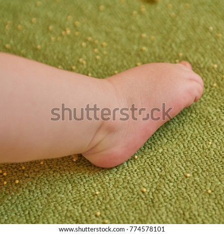 Babies, feet, body parts on green carpet #774578101