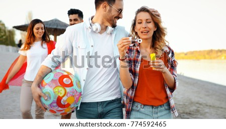 Beach party with friends. Cheerful young people spending nice time together on the beach #774592465