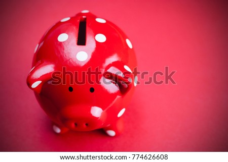 Piggy bank with polka dots - christmas expenses - savings money for gifts - economy and business, money bank on red background with copy space #774626608