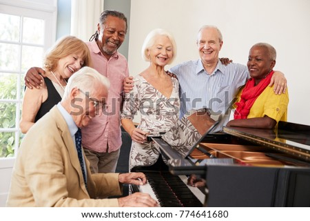 Group Of Seniors Standing By Piano And Singing Together #774641680