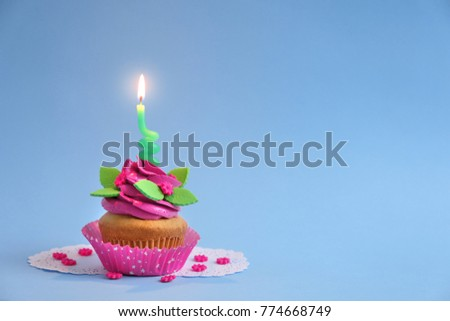 Beautifully decorated cupcake with candle on color background #774668749