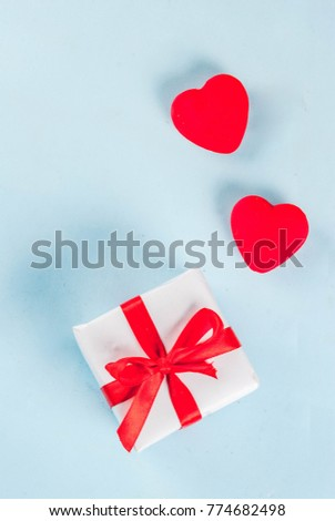Valentine's day light blue background with gift box with red ribbon and red hearts. Greeting card concept. Top view copy space #774682498