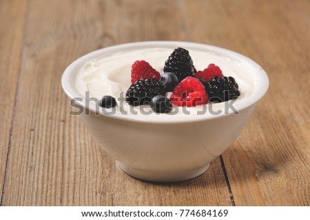 Composition of a typical genuine breakfast made with yogurt, blueberries, raspberries, blackberries, muesli. Concept of: fitness, diet, wellness and breakfasts. #774684169