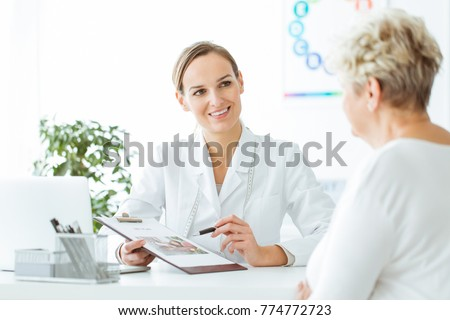 Smiling nutritionist showing a healthy diet plan to female patient with diabetes #774772723