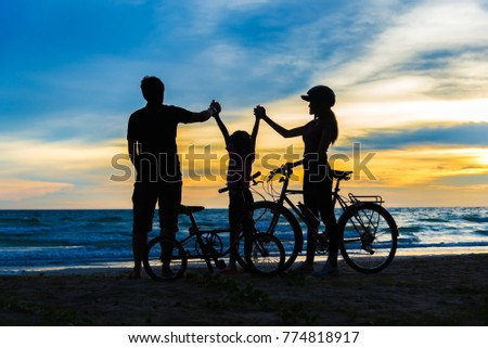 Biker family silhouette at the beach at sunset. #774818917
