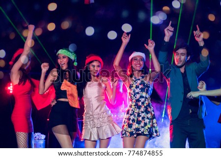 Group of young people celebrate new year party with spot light and fireworks in night party at club. selective focus on women in red dress. double exposure with bokeh background. #774874855