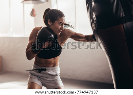 Female boxer hitting a huge punching bag at a boxing studio. Woman boxer training hard. #774947137